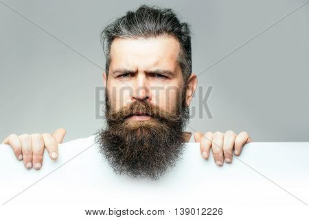 handsome bearded man with long lush beard and moustache on thougtful face with white paper sheet in studio on grey background copy space