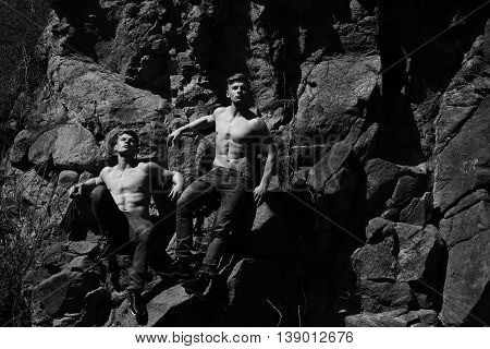 Muscular male twins men attractive young athletic shirtless in jeans pose black and white on mountain background