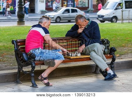 Lviv, Ukraine - 07/15/2016. Two men sitting on a bench in a park playing chess.
