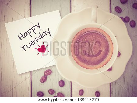 Happy Tuesday on paper note with coffee cup on table