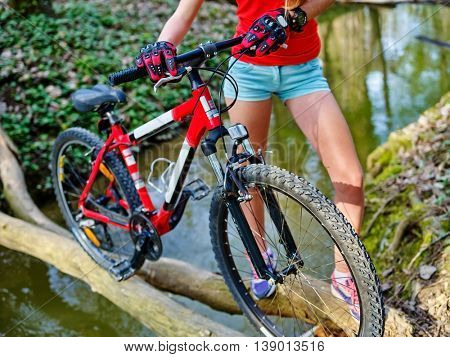 Middle part of bikes cycling girl. Girl rides bicycle. Girl cycling fording throught water on log . Cycling trip is good for health.