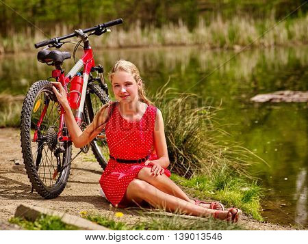 Bikes cycling girl. Girl wearing red polka dots dress rides bicycle into park. Girl in ecotourism. Girl sits on shore river water.