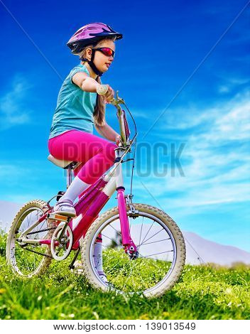 Bikes cycling child. Girl rides bicycle. Little girl in cycling. Cycling is good for child health. Cyclist look away aganist blue sky in park outdoor.