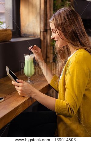 Woman using tablet and drinking milkshake in the cafe