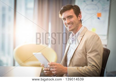 Portrait of businessman using digital tablet in the office