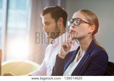 Thoughtful businesswoman with hand on chin while coworker working in the background