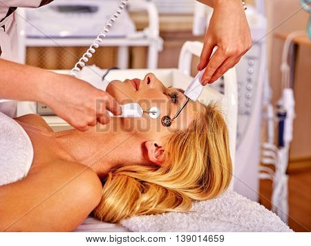 Young woman receiving electric galvanic face spa massage at beauty salon. Anti-aging facial massage.