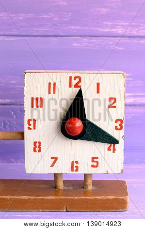 Old wooden clock toy for learning kids time. Second hand educational toy isolated on purple wooden background. Marks and scratches from general use