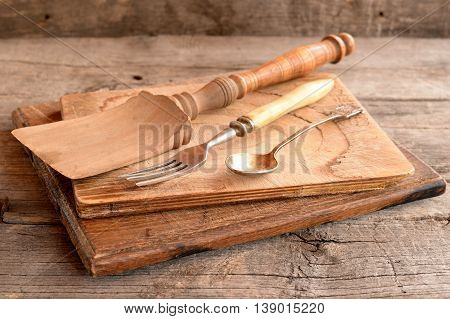 Simple vintage kitchen utensils on wooden background. Two cutting boards, fork, teaspoon, spatula on a wooden table. Rustic style