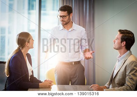 Businessmen and businesswoman interacting at their desk in the office