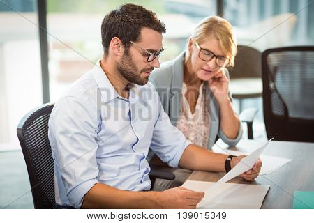 Businesswoman and a colleague reading document in the office