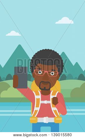 An african-american man making selfie on the background of mountains. Man with backpack taking photo with cellphone. Vector flat design illustration. Vertical layout.