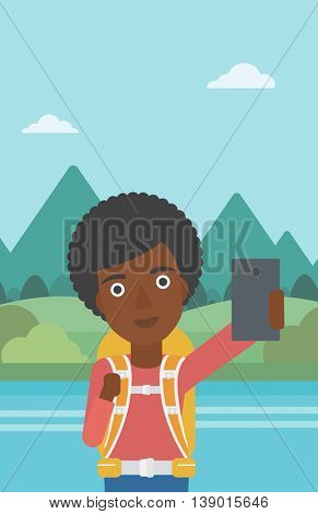 An african-american woman making selfie on the background of mountains. Travelling woman with backpack taking photo with cellphone. Vector flat design illustration. Vertical layout.