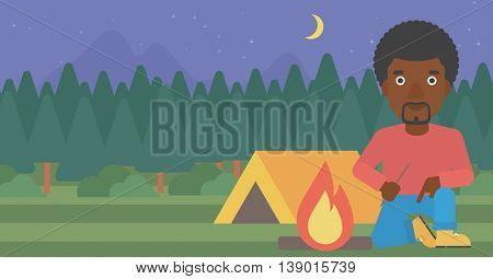 An african-american man kindling a campfire on the background of camping site with tent. Tourist relaxing near campfire. Vector flat design illustration. Horizontal layout.