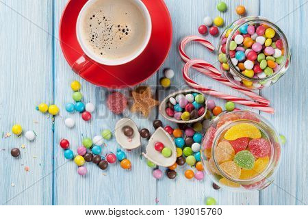Colorful candies and coffee cup on wooden table background. Top view