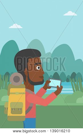 An african-american man taking photo of landscape with mountains. An african-american man with backpack taking photo with his cellphone. Vector flat design illustration. Vertical layout.