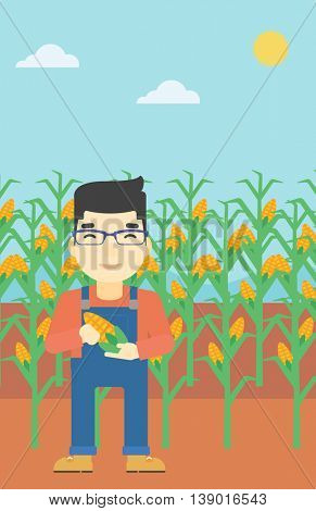 An asian farmer holding a corn cob. Young farmer standing on the background of corn field. Vector flat design illustration. Vertical layout.