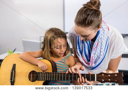 Close-up of teacher assisting girl to play guitar whiteboard in classroom