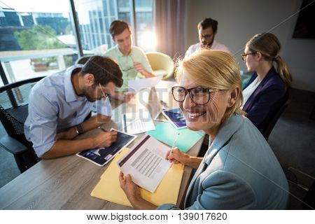 A colleague smiling at camera while coworker discussing over graph during a meeting in the office