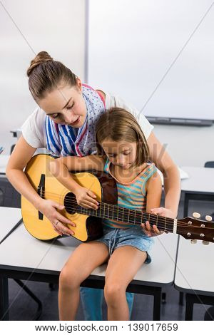 Young teacher assisting girl to play guitar in classroom