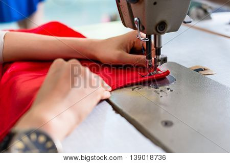 Womans hands using sewing machine in tailor workshop