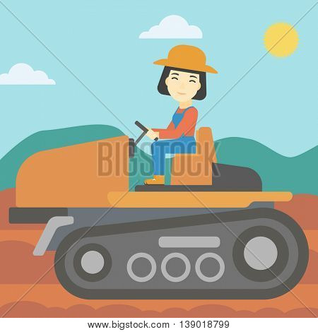 An asian female farmer driving a tractor on the background of plowed agricultural field. Farmer sitting on a tractor in the countryside. Square layout.
