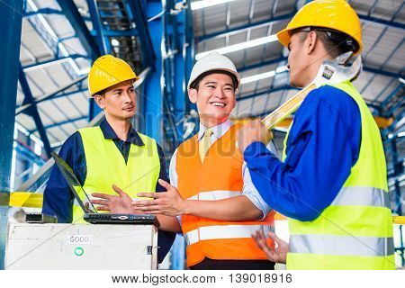 Team of workers and engineer  in Factory at production training with laptop