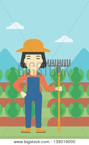 An asian female farmer holding a rake. Friendly farmer standing on the background of cabbage field. Vector flat design illustration. Vertical layout.