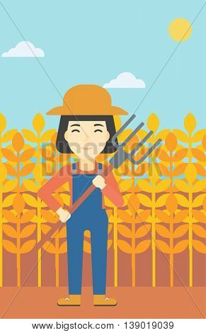 An asian female farmer holding a pitchfork. Smiling Farmer standing on the background of wheat field. Vector flat design illustration. Vertical layout.
