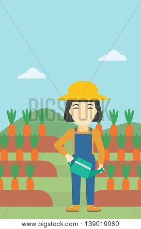 An asian female farmer holding a watering can. Farmer watering carrots. Female farmer standing on the background of carrots growing on field. Vertical layout.