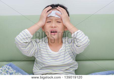 Little sick boy with headache sitting on sofa