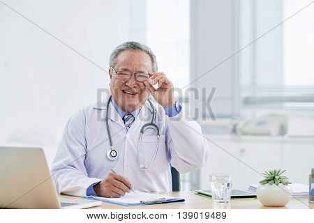 Portrait of cheerful Asian practitioner at his table