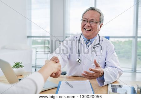 Vietnamese aged doctor greeting his patient before check-up