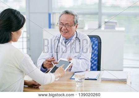 Mature general practitioner showing something on tablet computer to his client