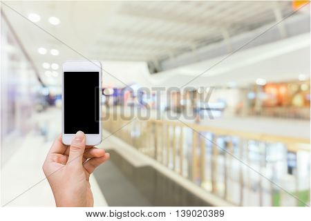 Smart phone with white screen in hand on blurred in shopping mall background shopping online concept shopping by smart phone