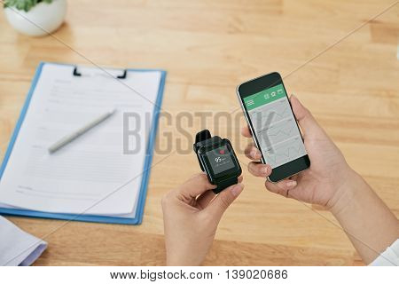 Hands of person checking medical information on his smartphone and watch