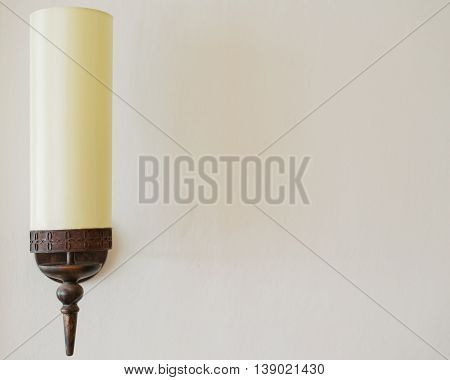 A solitary lamp on a pale textured wall