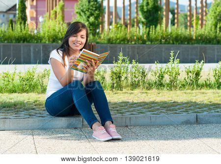 Girl Sitting Down And Reading From Notebook Or Diary