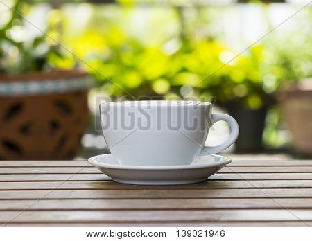 Coffee cup on wooden table, soft focus
