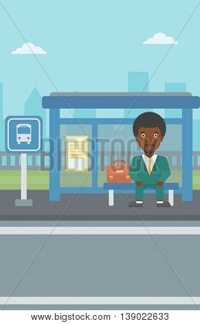 An african-american young man waiting for a bus at a bus stop on a city background. Young man sitting at the bus stop. Vector flat design illustration. Vertical layout.