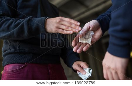 drug trafficking, crime, addiction and sale concept - close up of addict buying dose from drug dealer on street