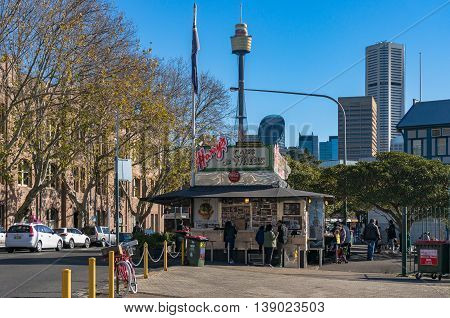 Sydney Australia - Jul 03 2016: Harry's Cafe de Wheels is an iconic pie cart on Cowper Wharf Road with cityscape on the background. They are best known for their meat pie