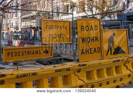 Sydney Australia - Jul 3 2016: Dowling Street footpath closure. Bright yellow road sign with arrow indicating pedestrian detour and road work area