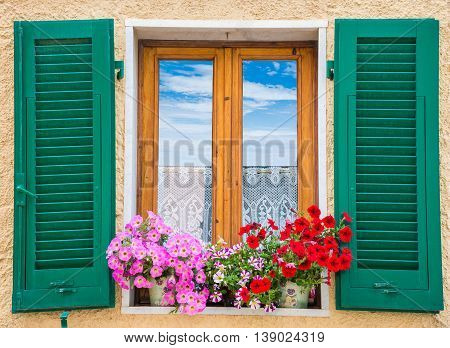 Traditional architecture of the walls decorated by flowers arround the window, in Capoliveri town, Italy
