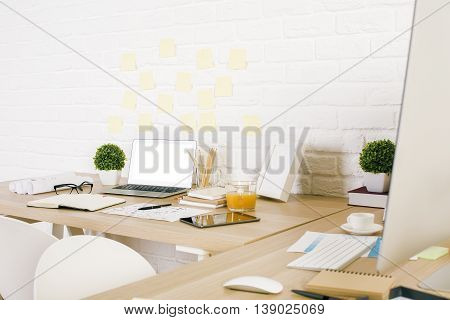 Side view of creative designer workplace with various stationery and decorative items laptop with blank white screen and other electronic devices on white brick background. Mock up