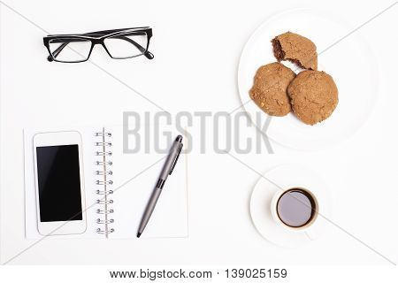 Top view of office desktop with blank cellular phone notepad and pen coffee cup cookies on plate and glasses. Mock up