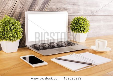 Side view of creative wooden desktop with blank white laptop smartphone notepad with pen coffee cup and decorative plants. Mock up