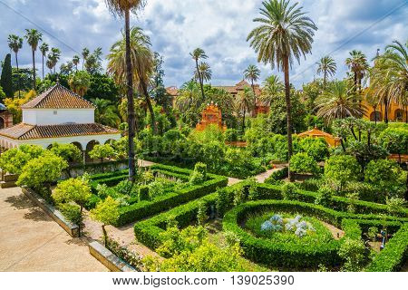 Romantic public garden of Seville palace in a day time. Traditional medieval design inside a Royal Palace in Andalusia Spain