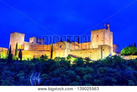 Panoramic view of Alhambra palace on the hill illuminated at night in Granada - Andalusia Spain