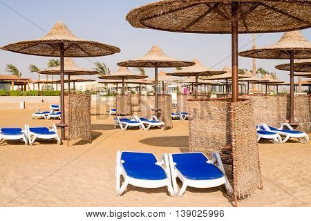 Covered blue recliners on sandy beach. Horizontal